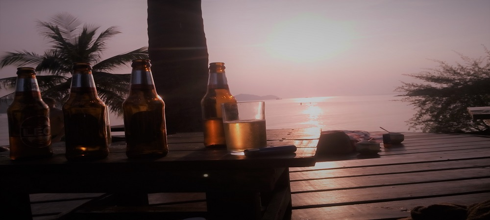 Beach Sunset in background & Beer on table in foreground